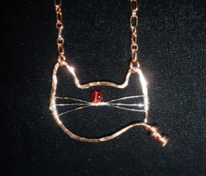 Mr. Kitty; hammered copper with red glass heart nose and sterling silver whiskers.