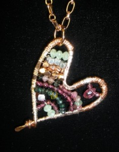 Hammered copper heart with ruby, garnet, emerald, crystal, fine silver.